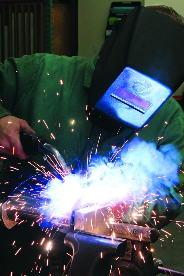 Kevin Ray welds a component to be used with a plunger mechanism manufactured by Quantum Engineered Products, Inc. in Saxonburg.